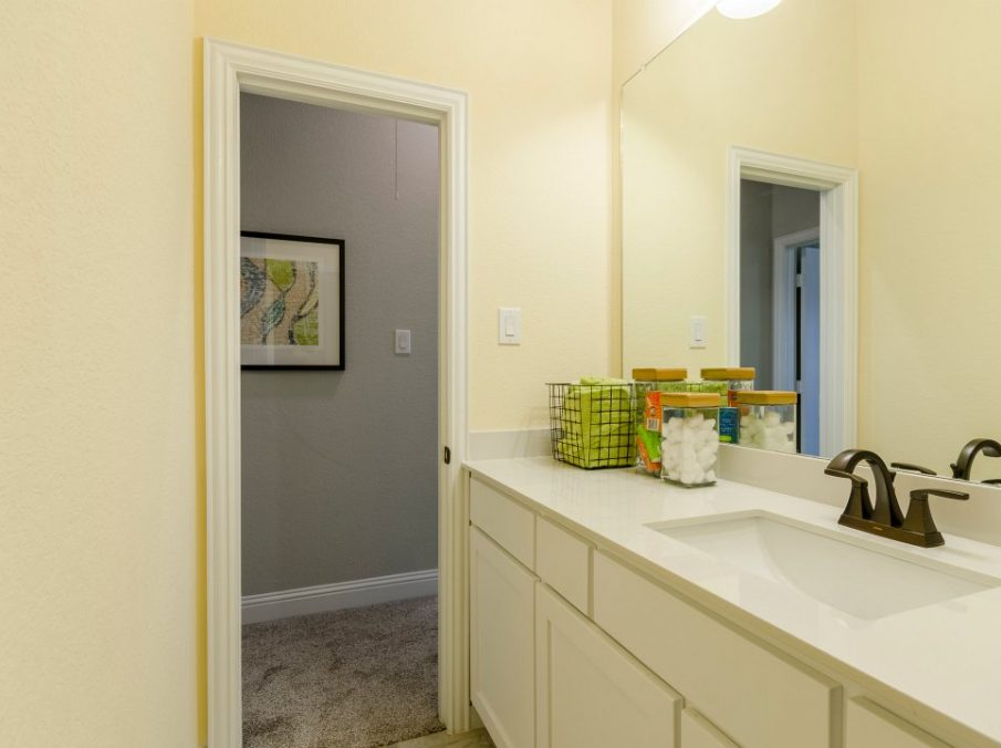 Landon Homes new home builder 432 Carrington Kids Bath with yellow walls and white painted cabinets